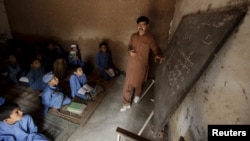 A man teaches students at a school in Kababiyan refugee camp in Peshawar, Pakistan, on October 6.