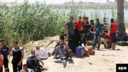 Displaced Iraqis who were forced to flee their hometowns ahead of gains made by Islamic State (IS) militants in Ramadi wait near the Bzaybiz bridge crossing the Euphrates River on their way to Baghdad, May 16, 2015