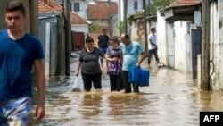Луѓе поминааt низ надојдените води на 7 август 2016 година во селото Стајковци, близу Скопје, по поројните дождови и силните бури во текот на ноќта.