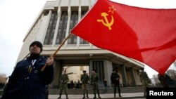 Чоловік з радянським прапором біля будівлі парламенту Криму, 6 березня 2014 року