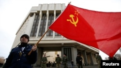 A man holds a Soviet flag as he attends a pro-Russian rally at the Crimean parliament building in Simferopol on March 6.
