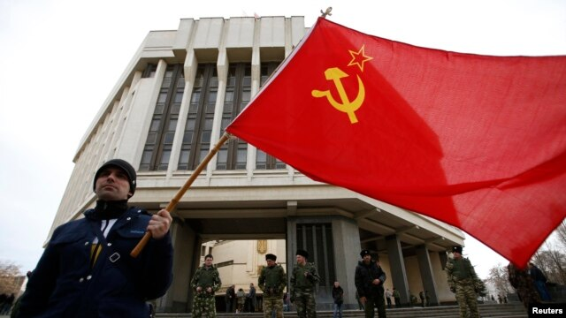 A man holds a Soviet flag as he attends a pro-Russian rally at the Crimean parliament building in Simferopol in March.
