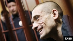 Russian artist Pyotr Pavlensky gestures inside a defendants' cage during a court hearing in Moscow in February.