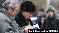Бишкектеги көчө дүкөнүндө китеп карап отурган кишилер.
