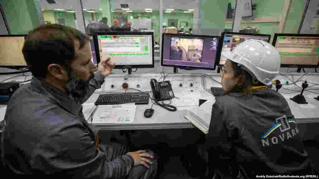 Two nuclear containment specialists inside the main control center at the New Safe Confinement (NSC). Some 3,000 people work at the site, including several foreign specialists.