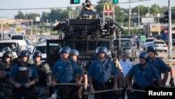 Полицейские стоят напротив протестующих в Фергюсоне. 14 августа 2014 года.