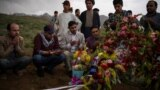 Friends and relatives of AFP photographer Shah Marai Faizi gather at his burial in Kabul on April 30 after his death in the second of two bombings that occurred in the Afghan capital.