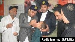 Афганские медицинские работники и сотрудники гуманитарной миссии ООН вакцинируют детей от полиомиелита.