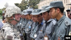 A US soldier congratulates Afghan police after training in Kabul