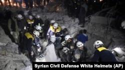 """Волонтеры """"Белых касок"""" разбирают завалы, разрушенного бомбой здания, в поисках людей"""
