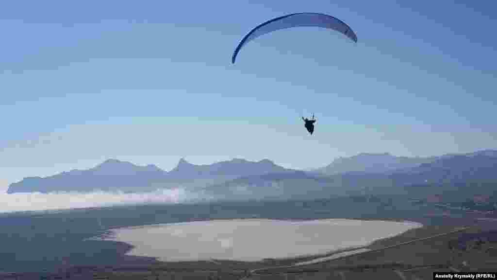 Под крылом параплана белеет высохшее соленое озеро Бараколь
