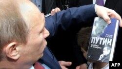 Владимир Путин держит в руках книгу о себе. Пенза, 9 марта 2011 года.