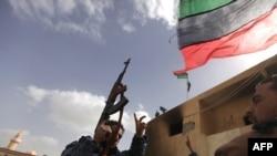 Ливиянын ички коопсуздук күчтөрүнүн мүчөлөрү Чыгыштагы Тобрук шаарында өлкөнүн эски желегин көтөрүп жүрүшөт, 24-февраль, 2011-ж.
