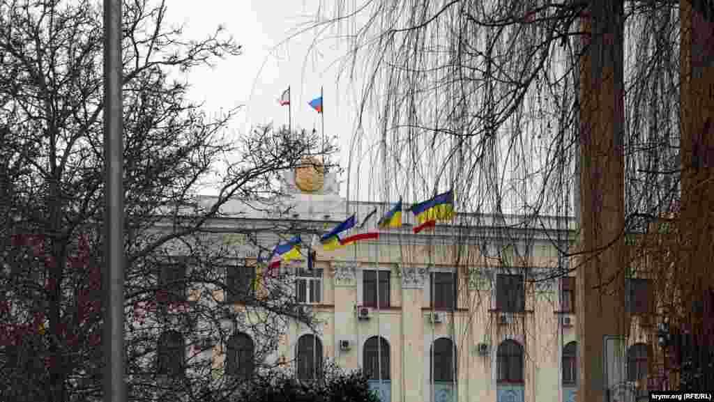 Последние украинские флаги в городе. «Ополченцы» бы их давно сорвали, но флагштоки стоят перед зданием Совета министров, в зоне оцепления, куда не пускает милиция. А «зеленые человечки» пока из Совмина и Верховной Рады так и не выглянули. В этот день, в пятницу, администрация школ в центре Симферополя рекомендовала школьникам пропустить занятия. Не приказала, а именно рекомендовала Это был последний день зимы 2014 года.