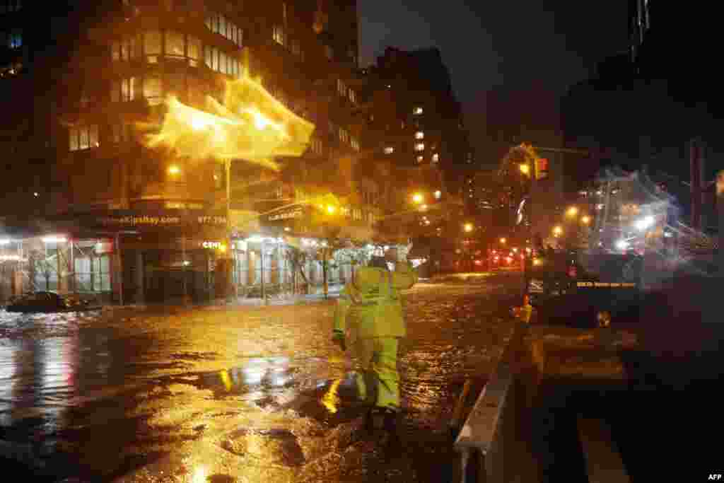 A Con Edison worker walks through the flood waters on the corner of 33th Street and 1st Street in front of NYU Langone Medical Center in Manhattan.