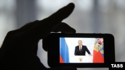 Russia -- A man watches a live TV broadcast of Russian President Vladimir Putin's address on his smartphone, in Ivanovo, December 3, 2015