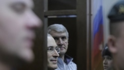 Mikhail Khodorkovsky and Platon Lebedev (center, left and right) look on from the dock of a Moscow courtroom on December 30.