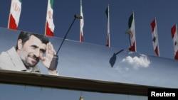 Iranian and Lebanese flags atop a billboard depicting Iranian President Mahmud Ahmadinejad in Beirut