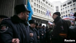 Ukrainian police separate ethnic Russians (right) and Tatars during rallies near the Crimean parliament building in Simferopol.