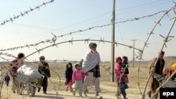 Афганские беженцы пересекают границу с Пакистаном.