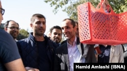 Former Iranian Vice President Hamid Baghaei (holding bag) greets supporters after his trial on October 22.