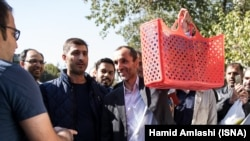 Former Iranian vice president and Ahmadinejad ally Hamidreza Baghaei showing a basket full of documents he carries to court on October 22, 2017.