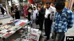 Көшеде газеттерге үңілген жұрт. Иран.