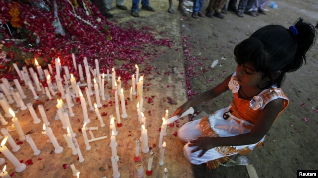 A girl lights a candle during a candlelight vigil for the victims of garment-factory fire in Karachi that killed at least 258 people.