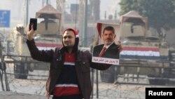 Египеттің биліктен тайдырылған президенті Мұхаммед Мурсидің суретін ұстап тұрған адам. Каир, 25 қаңтар 2015 жыл. (Көрнекі сурет.)