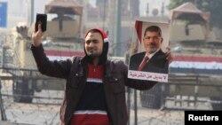 Сторонник свергнутого президента Египта Мохаммеда Мурси держит в руках портрет Мурси и Коран. Каир, 25 января 2015 года.