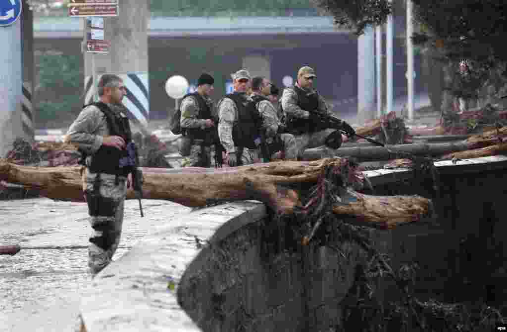 A handout picture provided by the Georgian prime minister's press office shows armed policemen patrolling a flooded street in Tbilisi.