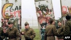 مأموران مرزی آلمان شرقی در حال برداشتن بخشهایی از دیوار برلین در ۱۱ نوامبر ۱۹۸۹ با هدف گشایش گذرگاهی میان قسمتهای شرقی و غربی برلین