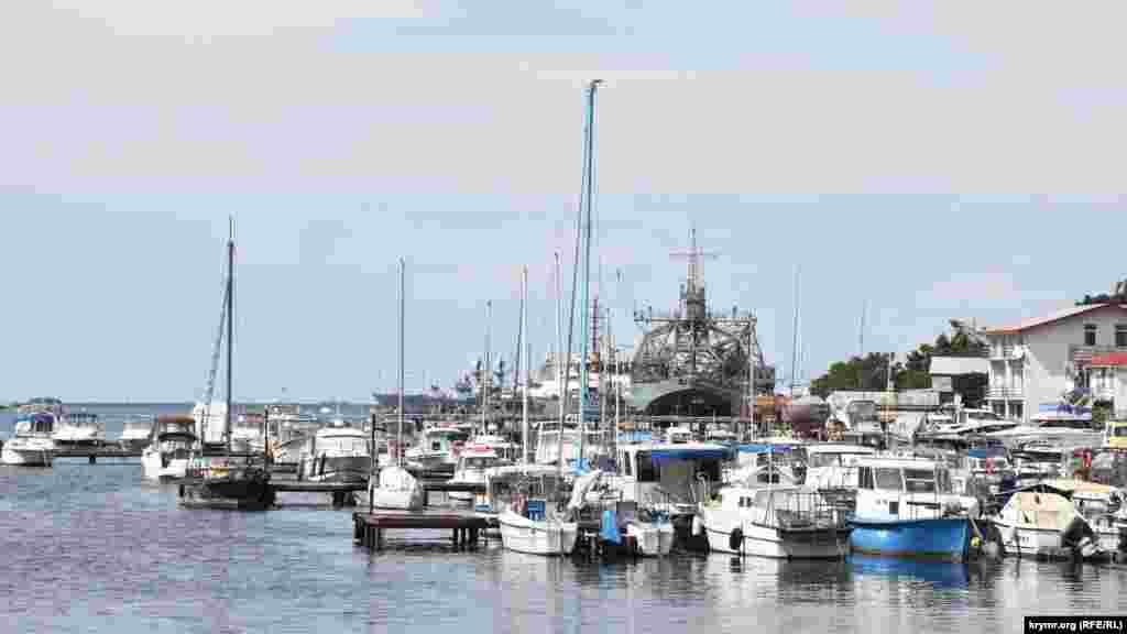 Стоянка яхт, яликів і рибальських човнів у Стрілецькій бухті. На задньому плані – кораблі Чорноморського флоту Росії