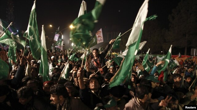 Supporters of Muhammad Tahirul Qadri, leader of Mihaj-ul-Quran, wave Pakistani flags during the protest in Islamabad on January 14.