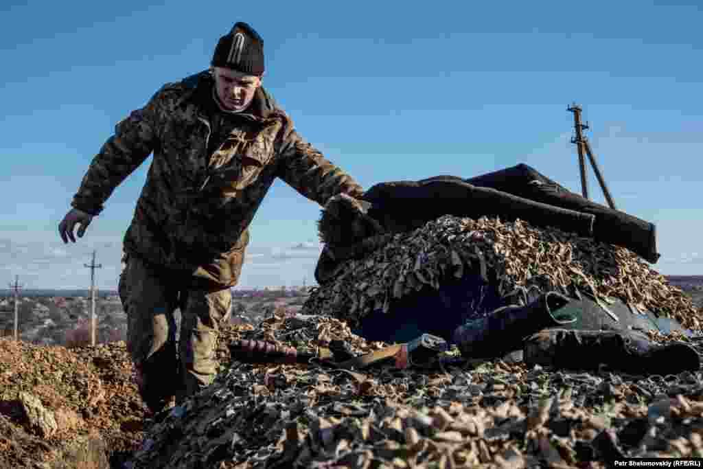 A Ukrainian government serviceman walks on top of an armored vehicle near Zaytseve.