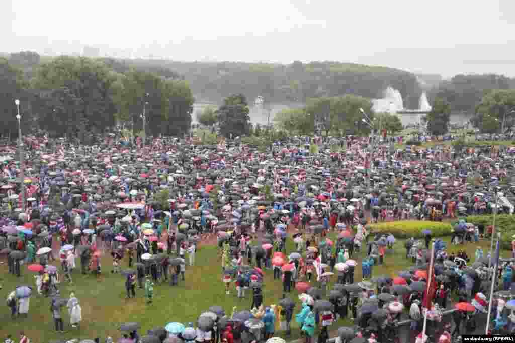 Людзі ў парку Перамогі, побач з Палацам Незалежнасьці
