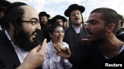Israel -- An ultra-Orthodox Jewish man (L) argues with a secular man during a protest against the government's pledge to curb Jewish zealotry in Israel, in the town of Beit Shemesh, near Jerusalem, 26Dec2011