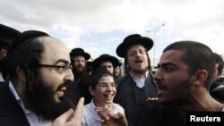 An Ultraorthodox Jewish man (left) argues with a secular man during a protest against the government's pledge to curb Jewish zealotry in Israel, in the town of Beit Shemesh, near Jerusalem, on December 26.