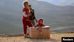 أطفال من عائلات أيزيدية في جبل سنجار قرب صندوق مساعدات غذائية
