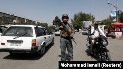Кабул көшесінде тұрған полиция қызметкері. Ауғанстан, 6 тамыз 2017 жыл.