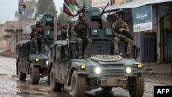 Iraqi pro-government forces patrol the eastern part of the embattled city of Mosul on December 28, during an ongoing military operation against Islamic State (IS) militants.