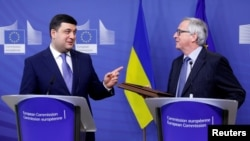 Ukrainian Prime Minister Volodymyr Hroysman (left) and European Commission President Jean-Claude Juncker hold a joint news conference in Brussels on February 10.