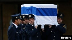 Members of the Knesset guard carry the flag-draped coffin of former Israeli Prime Minister Ariel Sharon before a memorial ceremony at the Knesset, Israel's parliament, in Jerusalem on January 13.