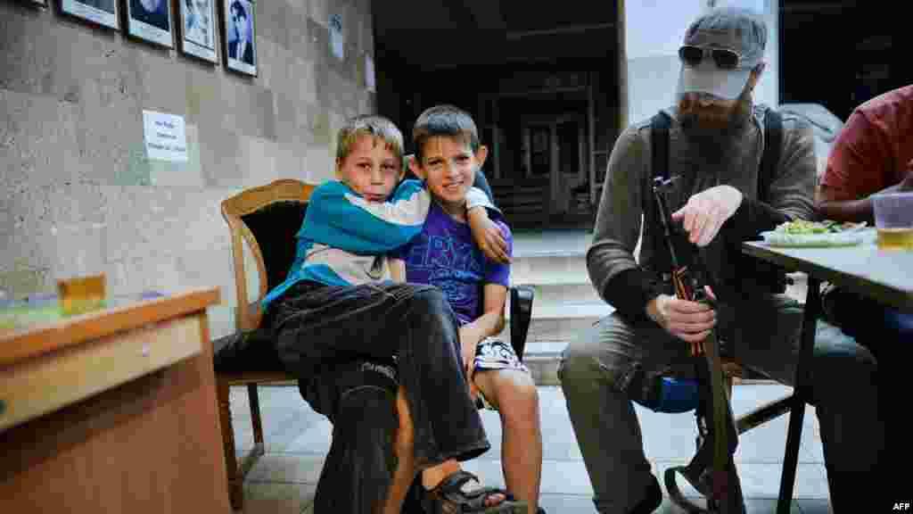 """Өзін өзі жариялаған """"Донецк халық республикасы"""" өкілдерінің қасында отырған балалар. 12 маусым 2014 жыл."""