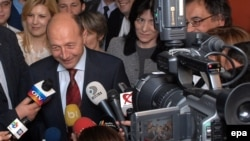 Romanian President Traian Basescu speaks to journalists while leaving his campaign headquarters in Bucharest on December 7.