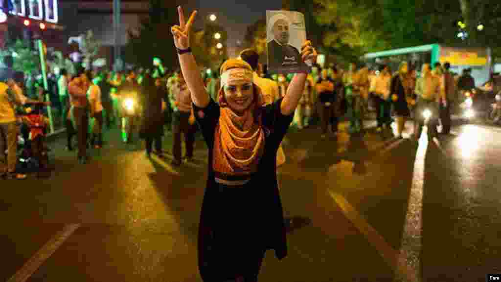 A woman flashes a victory sign alongside a photo of Rohani, a former military commander and lawmaker.