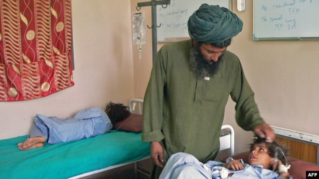 Abdul Ghaffar comforts his wounded child at a hospital in Kandahar on July 24.
