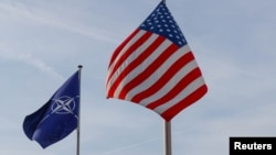 NATO and U.S. flags fly at the entrance of the alliance's headquarters in Brussels. (file photo)