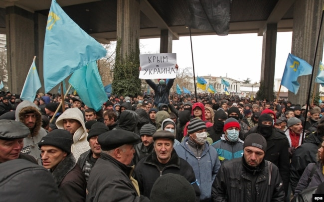 "Activists hold up Crimean Tatar flags and a banner reading ""Crimea = Ukraine!"" during a protest near the parliament building in Simferopol, Crimea, in February 2014."