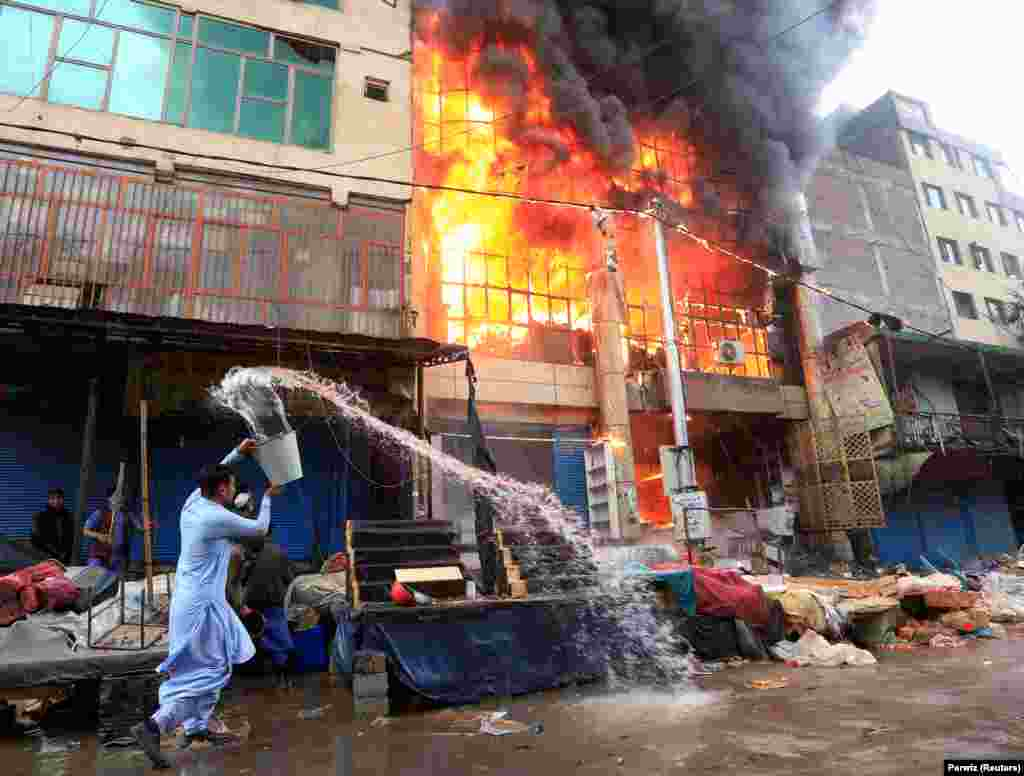 An Afghan man helps to prevent the spread of a big fire at a commercial market in Jalalabad. (Reuters/Parwiz)